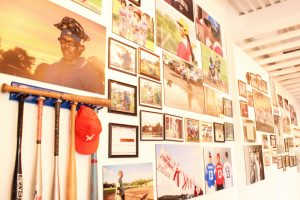 Baseball bats and old photos on a wall.